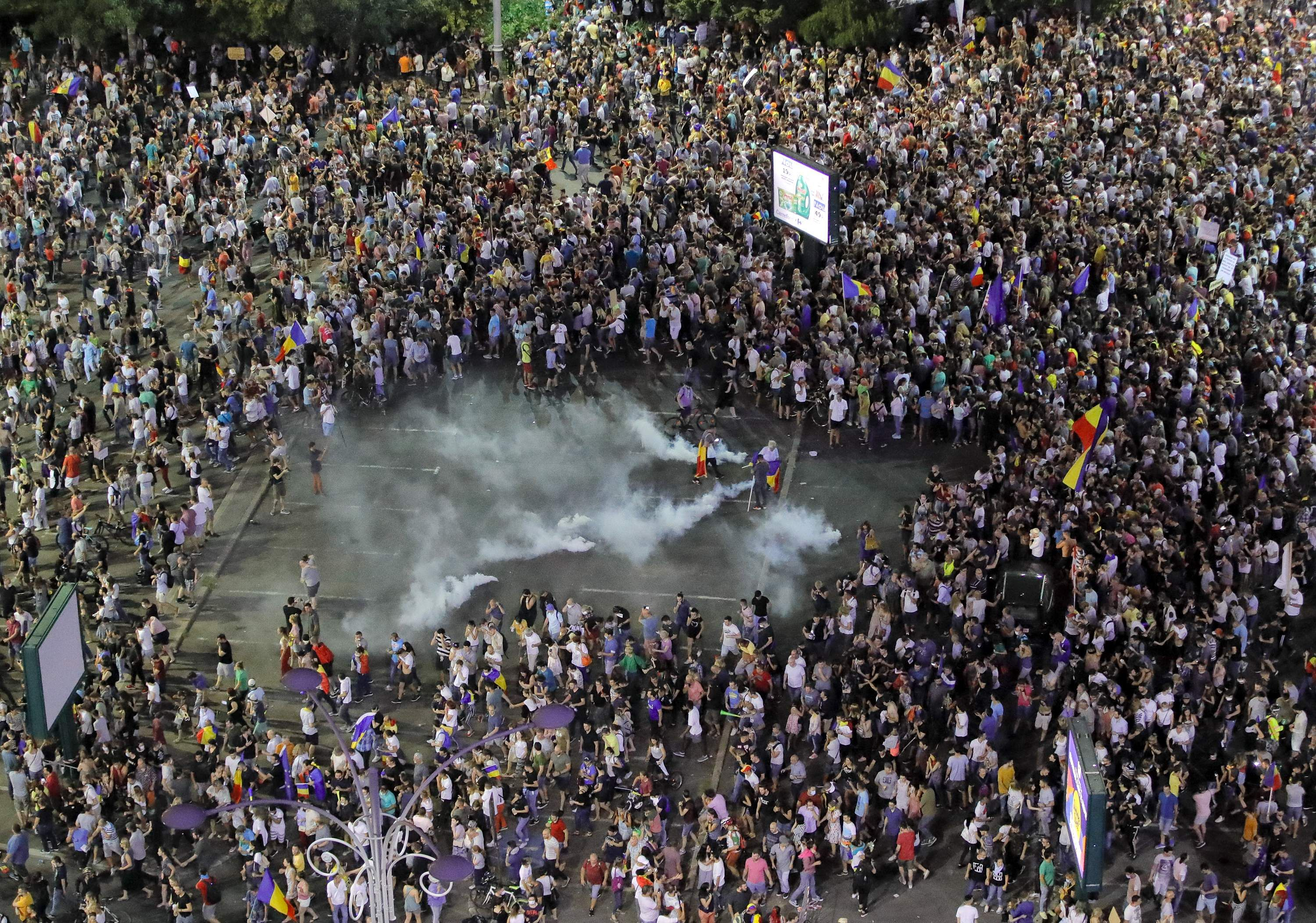 Protesters briefly clear the center of the square after riot police fired teargas outside the government headquarters in Bucharest Romania