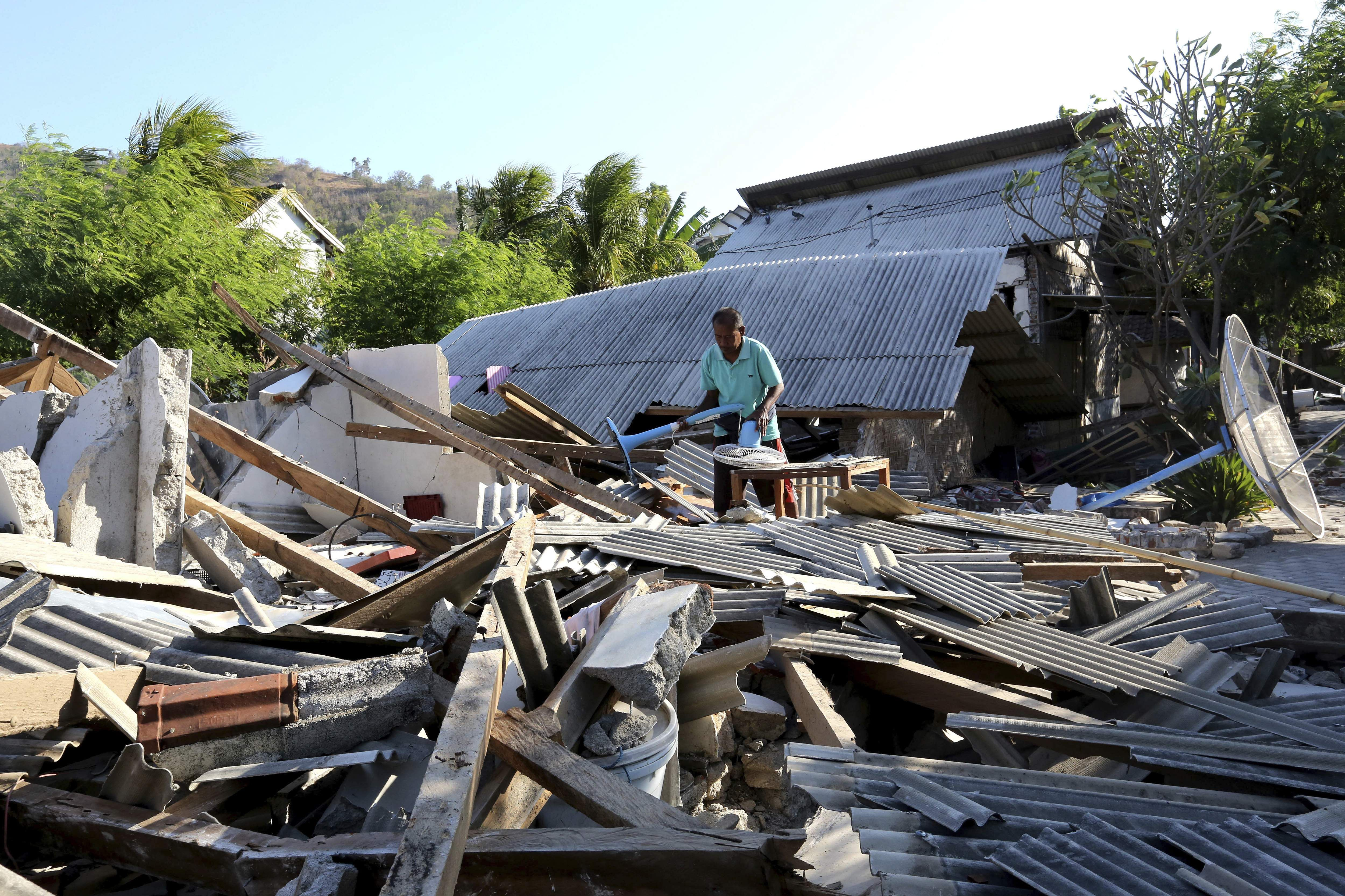 Usable items are salvaged from a home destroyed in an earthquake in North Lombok Indonesia
