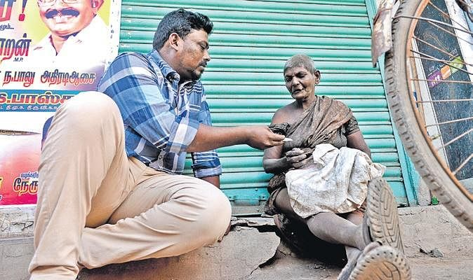 Arul lending money to a woman who lives on the footpath at Purusaiwalkam  in Chennai
