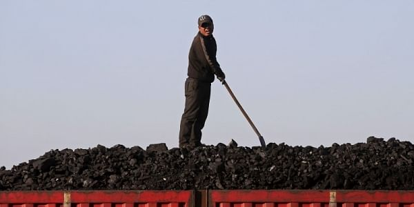 A worker speaks as he loads coal on a truck at a depot near a coal mine. (File photo | Reuters)
