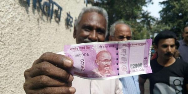 A man shows the new currency note in Kozhikode. ( Sanesh A. | EPS)