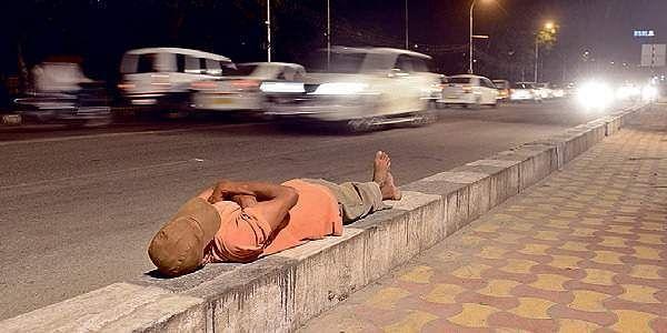 A homeless man sleeping on pavement