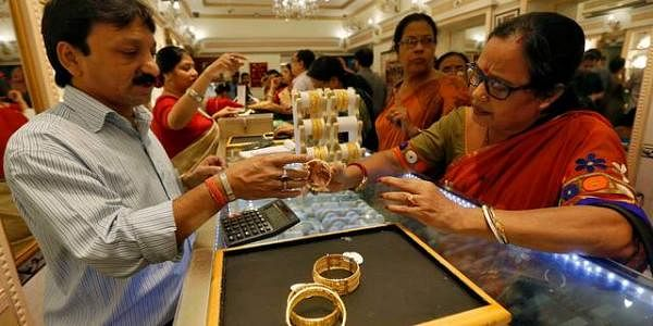 A salesperson displays ornaments to customers at a jewellery showroom in Ahmedabad. (File photo | Reuters)