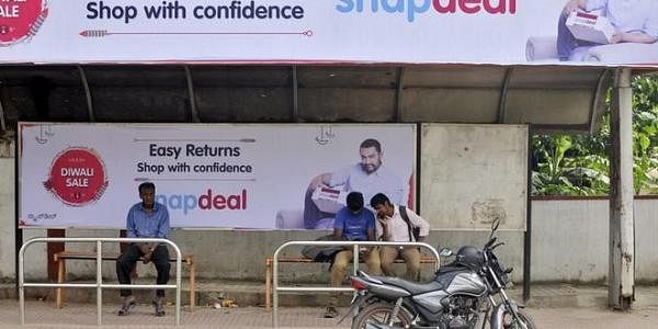 fa74a340a8d Commuters sit at a bus stop adorned with an advertisement of Indian online  marketplace Snapdeal featuring Bollywood actor Aamir Khan