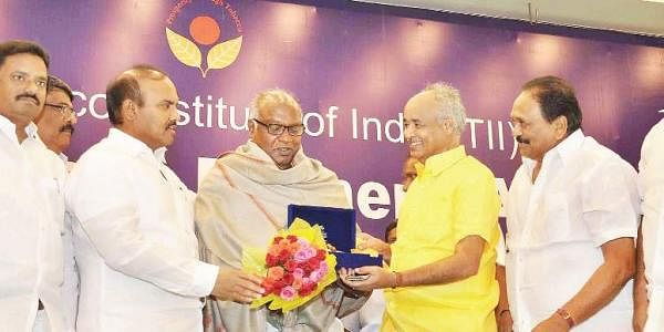 Agriculture minister P Pulla Rao presenting an award to a tobacco farmer during TII Tobacco Farmers' Awards  in Vijayawada on Friday | Express