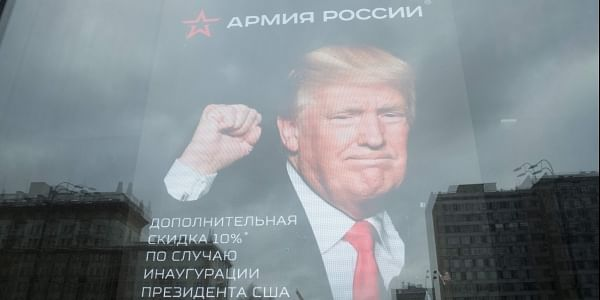 The US Embassy building is reflected in a window of a Russian military outerwear shop 'Armia Rossii' (Russian Army) displaying a poster of Donald Trump, in downtown Moscow, Russia. | AP