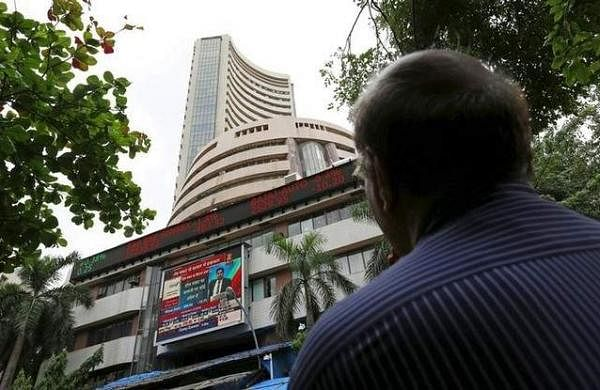 A man looks at a screen across a road displaying the Sensex on the facade of the Bombay Stock Exchange (BSE) building in Mumbai. (File photo | Reuters)