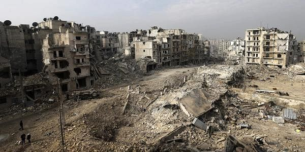 People walk through mounds of rubble which used to be high rise apartment buildings in Syria.(File photo | AP)