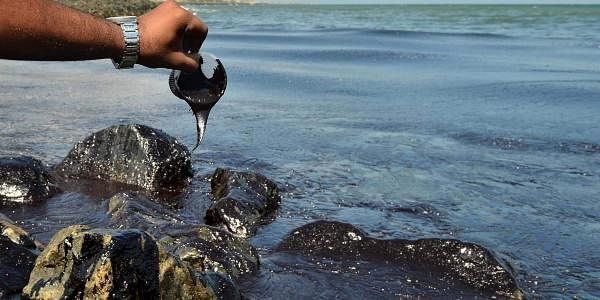Thick oil from the sea doesn't easily flow out of a plastic cup at Bharatiyar Nagar. (Photo | EPS)