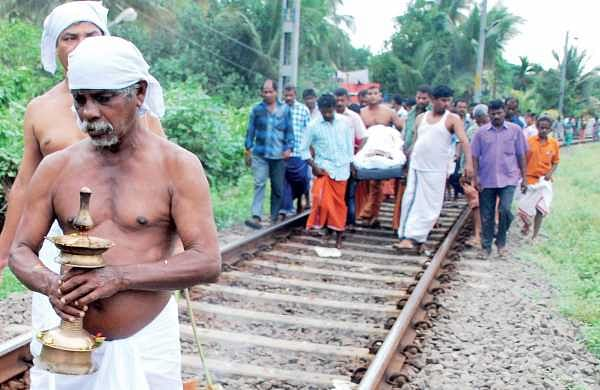 The funeral cortege of a man progresses with mourners carrying the body of the deceased down the rail tracks at Kammattipaadam near  Ernakulam South Station | k shijith