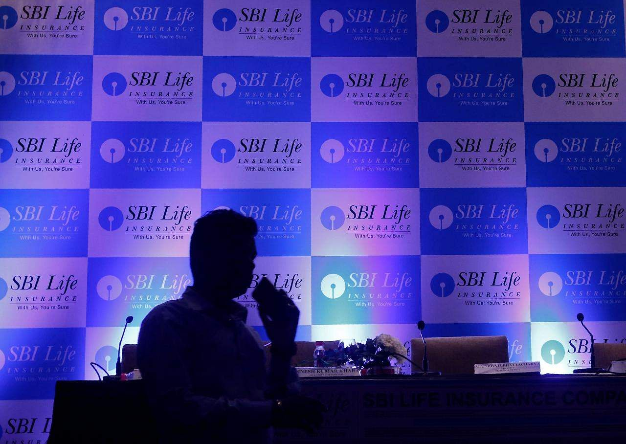 A man walks past a podium set up at the venue of a news conference to announce the launch of Initial Public Offering by SBI Life Insurance Co in Mumbai, September 13, 2017. REUTERS/Shailesh Andrade/Files