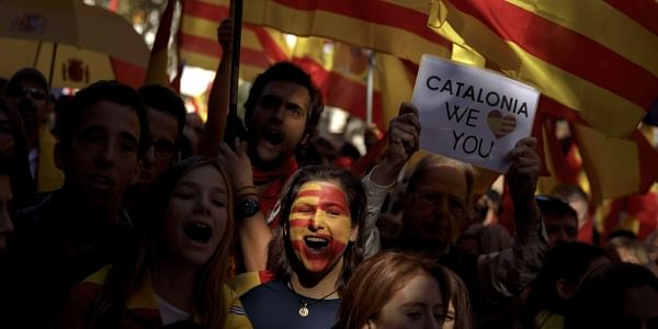 A woman with the Senera and Spanish flags painted on her face shouts slogans as she takes part in a rally against Catalonia's declaration of independence, in Barcelona, Spain, Sunday, Oct. 29, 2017.