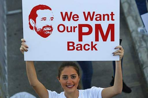 A Lebanese woman holds a placard supporting the outgoing Lebanese Prime Minister Saad Hariri to return from Saudi Arabia during the Beirut Marathon, in Beirut, Lebanon.|AP