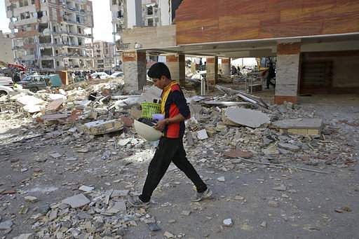 An earthquake survivor carries his belongings in front of damaged buildings, in a compound which was built under the Mehr state-owned program, in Sarpol-e-Zahab in western Iran. AP