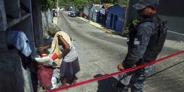 A homeless woman that was sleeping on the street leaves a police secured the area where a man and a woman were found murdred inside a bar in downtown Acapulco, Guerrero state, Mexico.|AP
