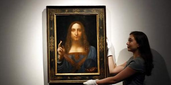 An employee poses with Leonardo da Vinci's 'Salvator Mundi' on display at Christie's auction rooms, in London.|AP
