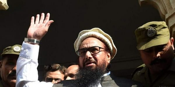 Pakistan head of the Jamaat-ud-Dawa (JuD) organisation Hafiz Saeed waves to supporters as he leaves a court in Lahore.|AFP