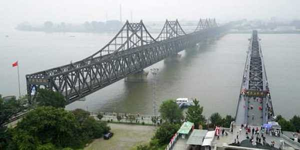 Visitors walk across the Yalu River Broken Bridge, right, next to the Friendship Bridge connecting China and North Korea in Dandong in northeastern China's Liaoning province.|AP