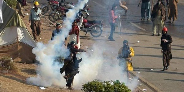 A Pakistani protester of the Tehreek-i-Labaik Yah Rasool Allah Pakistan (TLYRAP) religious group throws a tear gas shell back towards police during a clash in Islamabad.|AFP