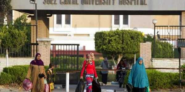 People walk outside the Suez Canal University hospital where injured worshippers an attack on a mosque receive treatment.|AP