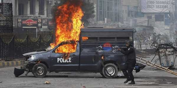 A Pakistani police officer aims his gun towards the protesters next to a burning police vehicle during a clash in Islamabad Pakistan. PTI