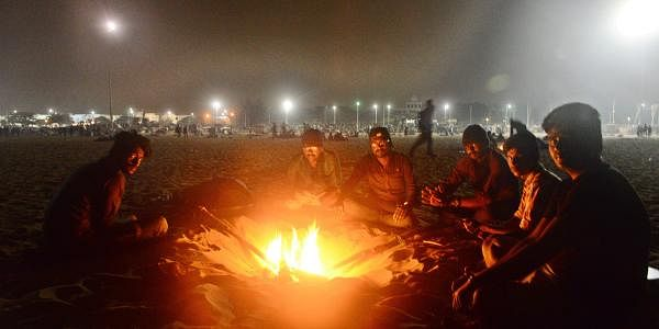 Protestors sit around a bonfire to protect themselves from the cold winter air at Marina Beach. Most of them have been staying overnight on the beach sands over the past few days to ensure continued support for the demonstration against the ban of Jallika