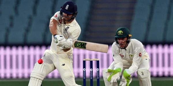 England's batsman Dawid Malan plays a shot as Cricket Australia XI's wicketkeeper Tim Paine (R) looks on during the first day of a four-day Ashes tour match at the Adelaide Oval.|AFP
