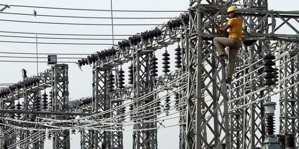 An employee works on electric pylons at a power station in Greater Noida on the outskirts of New Delhi. | REUTERS