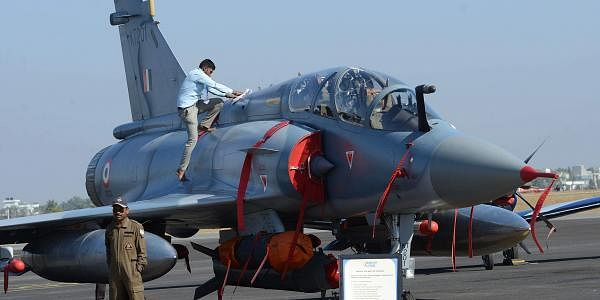 A staff member cleans a Mirage 2000 at the Aero India air show in Bengaluru. (Pushkar V | EPS)