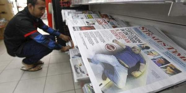 A man arranges a newspaper carrying Kim Jong-nam's death investigation report in Malaysia. (Photo | AP)