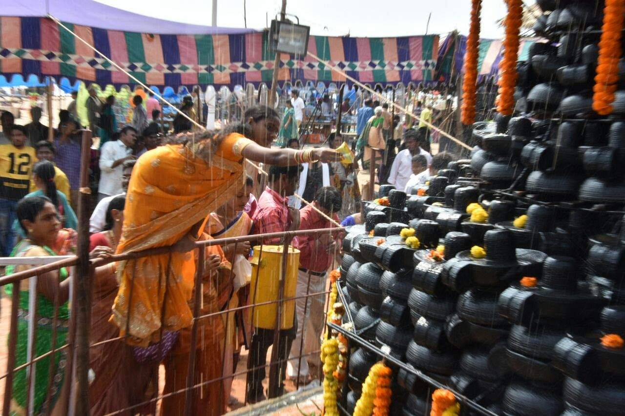 A devotee determined to pour milk over a Shiva Linga made of many smaller Shiva Lingas, stands on the railing around the deity on the sea shore in Vishakhapatnam on Maha Shivaratri on Friday. (RVK Rao | EPS)
