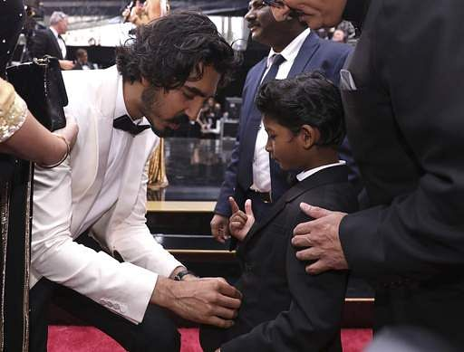 Dev Patel, left, buttons the jacket of his co-star Sunny Pawar at the Oscars on Sunday, Feb. 26 at the Dolby Theatre in Los Angeles. (Photo | AP)