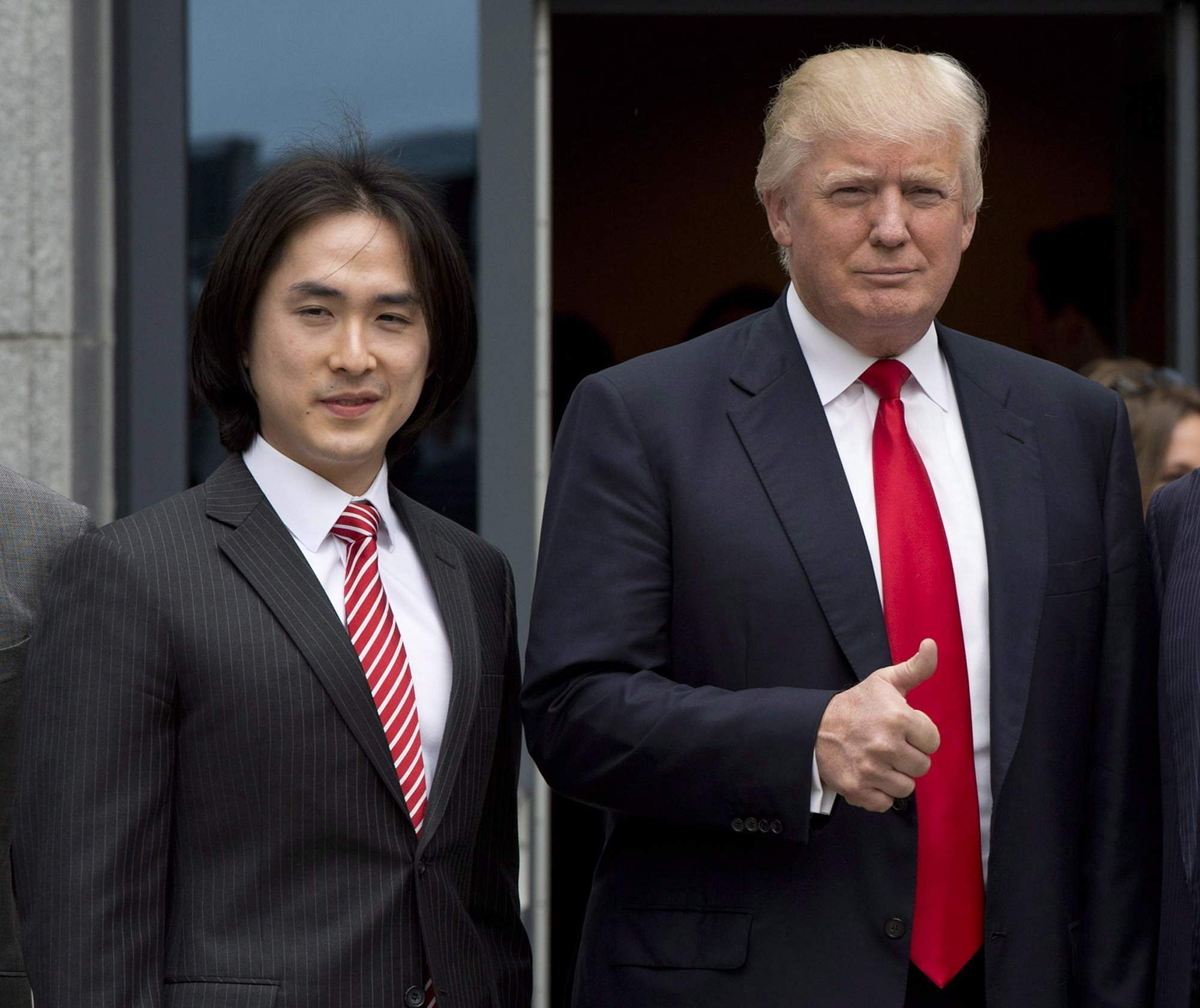 Donald Trump gives a thumbs-up as he poses with Tiah Joo Kim, left, CEO and president of Holborn Group, upon arrival to announce the building of Trump International Hotel and Tower Vancouver in downtown Vancouver, Canada. (File Photo | AP)