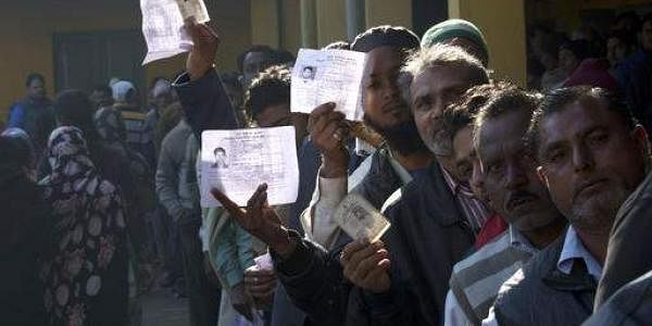 Uttar Pradesh polls: Indian voters show their identity card as they wait in a queue to cast their votes.