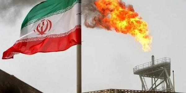 Gas flare on an oil production platform in the Soroush oil fields is seen alongside an Iranian flag in the Gulf. (Photo | Reuters)