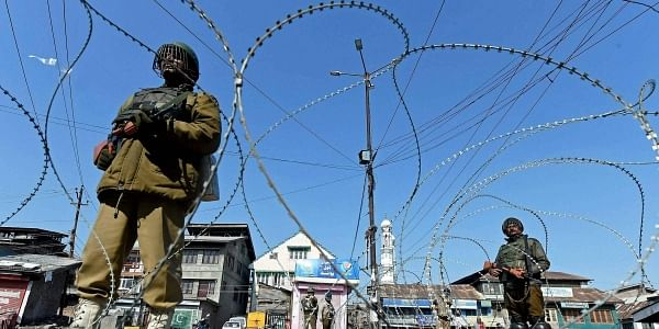 Security jawans stand guard near a razor wire during restrictions imposed by authorties as separatist groups have called for a general strike against Afzal Guru's hanging in Srinagar on Thursday. Separatists are pressing for the handing over to the family