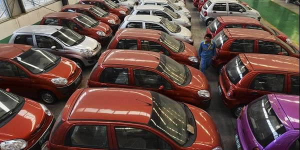 A worker walks among electric cars in a factory in Zouping county in eastern China's Shandong province. (File Photo | AP)