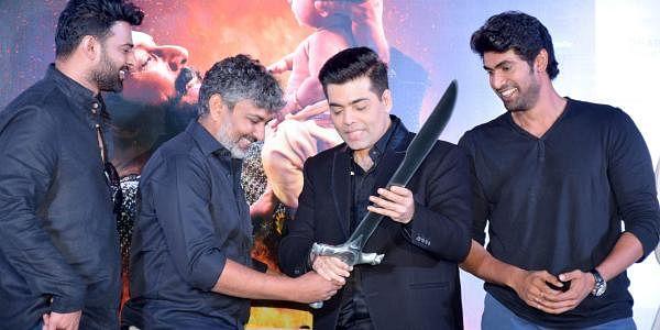 Flanked by lead actors Prabhas and Rana Daggubati, SS Rajamouli presents filmmaker Karan Johar with the sword used in the film (Arun Jetlie | EPS)