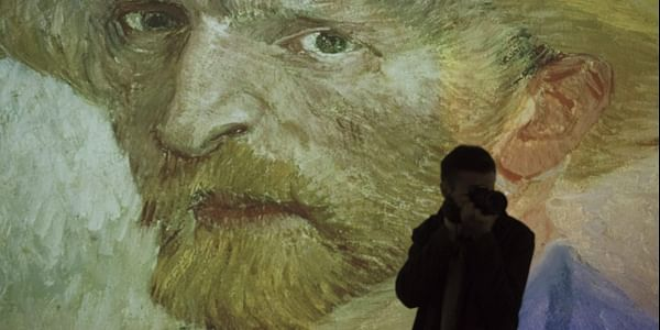 A man takes pictures in front of a video projection of a painting in the exhibition 'Monet 2 Klimt' in Dresden, Germany. (File   AP)