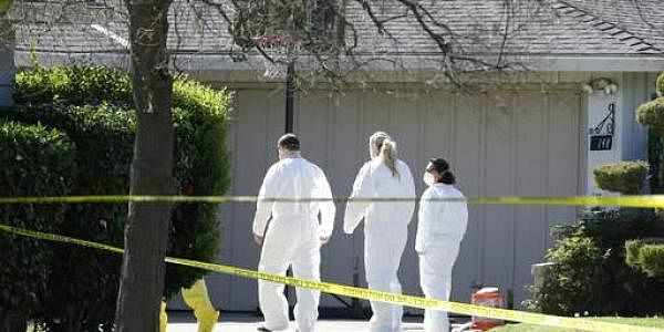 Investigators walk to the home where four people were found dead in California on March 23. (Photo | AP)