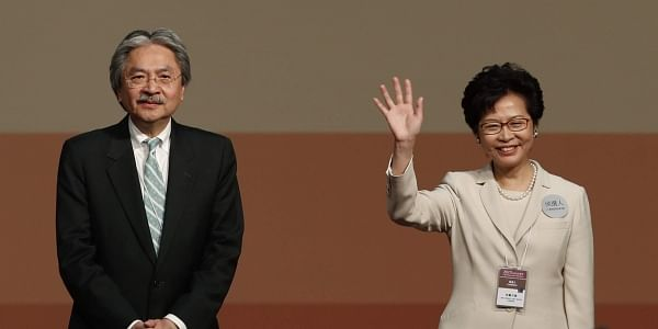 Former Hong Kong Chief Secretary Carrie Lam, right, waves as she declares her victory in the chief executive election of Hong Kong while former Financial Secretary John Tsang stands. (Photo | AP)
