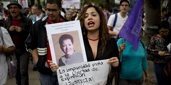 A woman shouts slogans holding a photo of Mexican journalist Miroslava Breach, gunned down, and a sign that reads in Spanish: 'the impunity kills freedom of speech, justice,'. (Photo | AP)