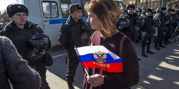 A woman with a Russian national flag walks past a Police line in Pushkin Square, downtown Moscow, Russia, Sunday, March 26, 2017. (File | AP)