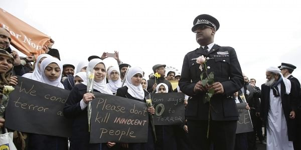 A police officer stands next to muslim girls during a commemorative event to mark last week's attack outside Parliament. (Photo | AP)
