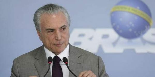 Brazil's President Michel Temer adjusts his microphones during a press conference at the Planalto Presidential Palace, in Brasilia, Brazil, Monday, Feb. 13, 2017, where he spoke on the security vacuum created by a 'police halt' in the Brazilian state Espi