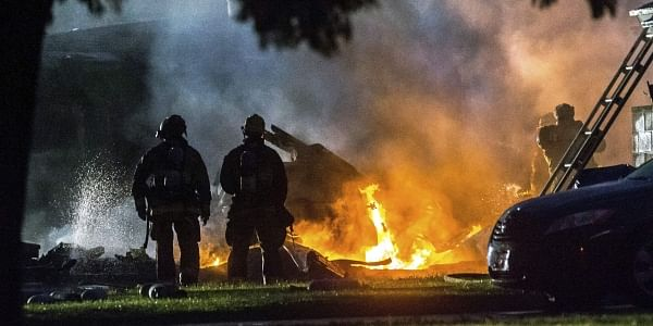 Firefighters put out flames after a plane crashed in Riverside, Calif. The deadly crash injured several when a small plane collided with two homes Monday shortly after taking off from a nearby airport, officials said. | AP
