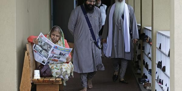 Men walk past a woman reading a newspaper at the Gurudwara Singh Sabha of Washington, a Sikh temple in Renton, Wash., Sunday, March 5, 2017, south of Seattle. (Photo | AP)