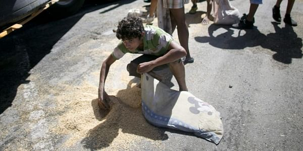 A youth uses his pillow as a bag to collect rice from the pavement at Puerto Cabello, Venezuela. (Photo | AP)