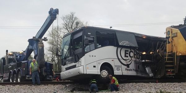 Men prepare to move a charter bus after it was crashed with a freight train, right, in Biloxi, Miss., Tuesday, March 7, 2017. (Photo | AP)