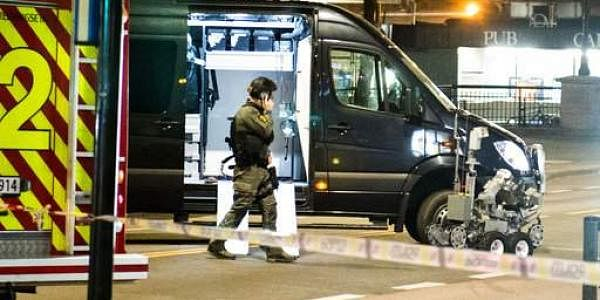 An officer works the scene as police cordon off a large area around a subway station on a busy commercial street in Norway on Saturday night. (Photo   AP)
